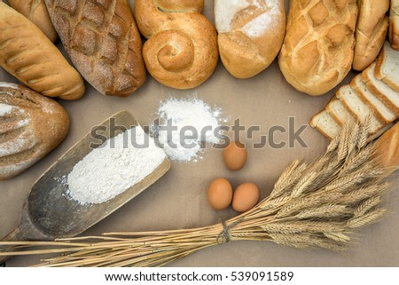 Various bread, wheat ears, scoop filled flour and eggs on brown background #539091589