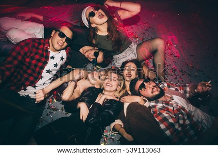 Group of friends at club lying on the floor and having fun. New year's party  #539113063