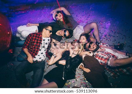 Group of friends at club lying on the floor and having fun. New year's party  #539113096