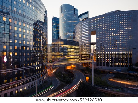 Night architecture. Skyscrapers with glass facade. Modern buildings in Paris business district. Evening dynamic traffic on a street. Business, economy and finances concept.  Copy space for text. Toned Royalty-Free Stock Photo #539126530