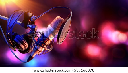 Close up studio condenser microphone with pop filter and anti-vibration mount live recording with color lights background. Side view #539168878