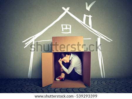 Sad woman sitting in a box house in search for shelter