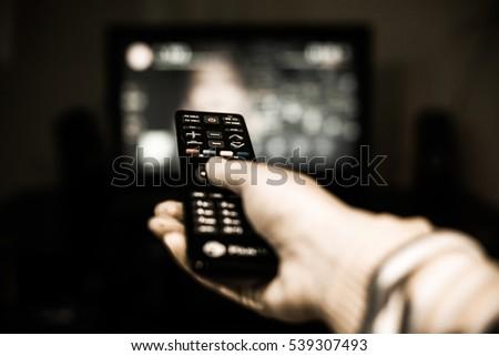 Remote control in hand before TV. Couch potato. #539307493