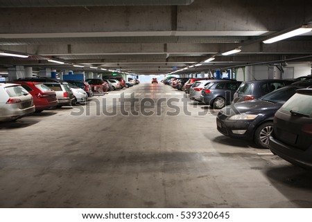Way to go out from covered free parking lot of city shopping mall. Cars standing in rows. #539320645