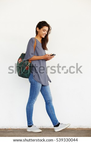 Full length portrait of beautiful young woman walking outside and reading text message on her mobile phone #539330044