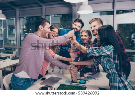 Happy businesspeople putting their fist on top of each other and laughing. They have training Royalty-Free Stock Photo #539426092