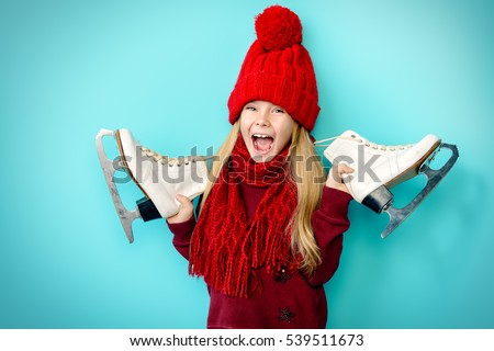Cheerful little girl in warm sweater and hat holding figure skates. Blue background.