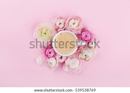 Morning cup of coffee and beautiful flowers on pink background from above in flat lay style