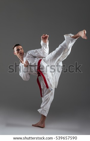 Photo of young sportsman dressed in kimono practice in karate isolated over grey background. Looking aside. #539657590