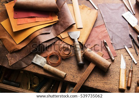 Leather craft or leather working. Selected pieces of beautifully colored or tanned leather on leather craftman's work desk .  Royalty-Free Stock Photo #539735062