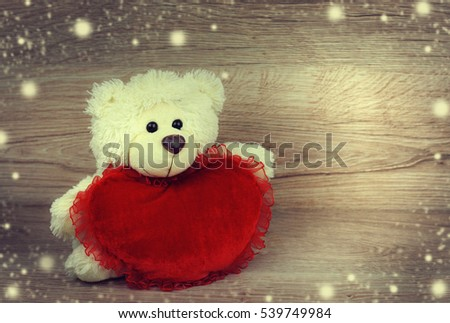 cute teddy bear with red heart on a wooden background