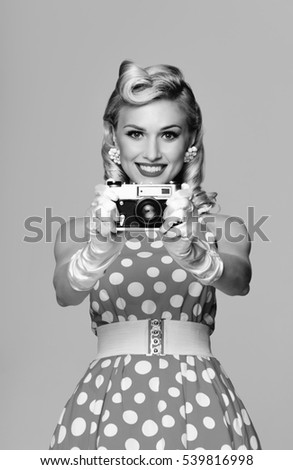 Portrait of beautiful young smiling woman, with no-name old film camera, taking picture, dressed in pin-up style. Caucasian blond model posing in retro fashion and vintage concept. Black and white.