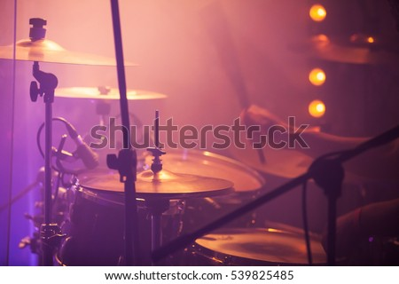 Live rock music background, drummer plays with drumsticks on rock drum set. Closeup photo, soft selective focus