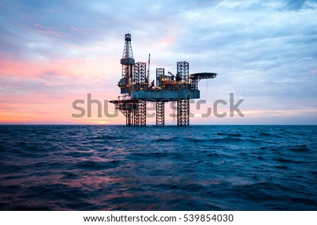 Offshore Jack Up Rig in The Middle of The Sea at Sunset Time #539854030