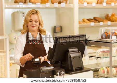 Swiping the card. Horizontal shot of a senior woman swiping your credit card at her bakery copyspace