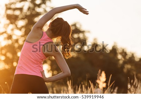 Young female workout before fitness training session at the park. Healthy young woman warming up outdoors. She is stretching her arms and looking away,hi key.