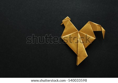 Golden shiny paper folded rooster handmade origami craft on black background. Nice natural holiday greeting card template. Empty space for text, copy, lettering.