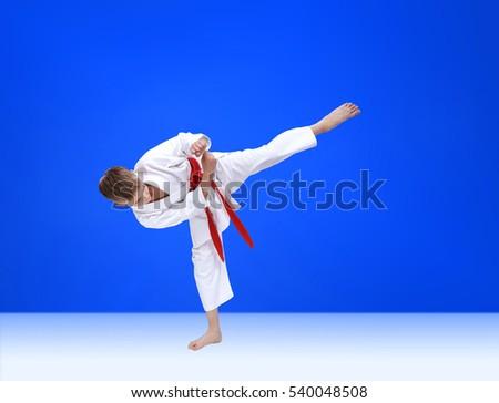 On a blue background karateka is beating kick leg #540048508