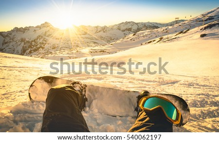 Snowboarder sitting on relax moment at sunset in french alps ski resort - Winter sport concept with person on top of the mountain ready to ride down - Legs view point with warm backlighting filter #540062197
