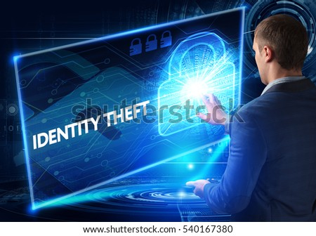 Business, Technology, Internet and network concept. Business man working on the tablet of the future, select on the virtual display: IDENTITY THEFT #540167380
