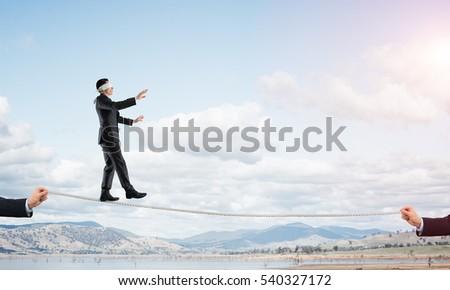 Businessman with blindfolder on eyes walking on rope over gap #540327172