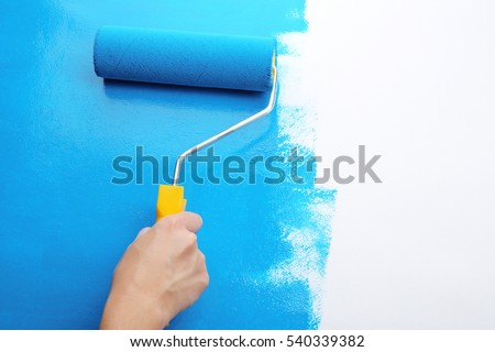 Decorator's hand painting wall with roller Royalty-Free Stock Photo #540339382