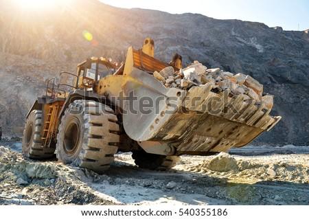 Wheel loader machine unloading rocks in the open-mine of iron ore #540355186