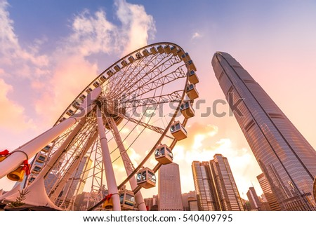 The popular icon Observation Wheel in Hong Kong island at sunset near Ferry Pier arera with landmark buildings in background. Royalty-Free Stock Photo #540409795