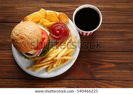 Tasty burger with snacks and coke on wooden table #540466225