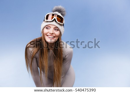 Attractive woman in winter cap gray sports thermal underwear for skiing training ski googles studio shot on blue.  #540475390
