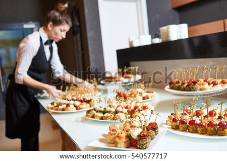 Restaurant waitress serving table with food #540577717