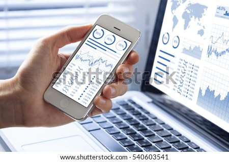 Investor analyzing stock market investments with financial dashboard, business intelligence (BI), and key performance indicators (KPI) on smartphone and computer screens #540603541