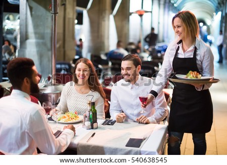 Portrait of smiling adult friends in outdoors restaurant and smiling waitress.  Focus on blonde girl #540638545