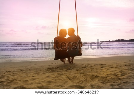 Romantic couple is sitting and kissing on sea beach on rope swing . Family vacation on honeymoon. Love and relationship Royalty-Free Stock Photo #540646219