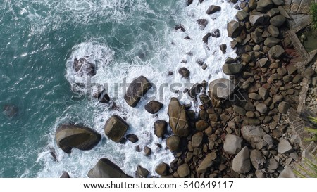 Aerial top view of sea waves hitting rocks on the beach in Phuket, Thailand #540649117