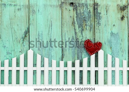 Blank rustic antique wood mint green sign with country red heart on white picket fence; Valentine's Day and love concept with painted wooden copy space