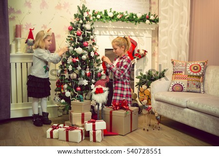 Little girls decorating Christmas tree and preparing gifts