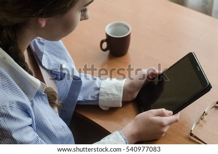 Girl sits at a table with a tablet. On the table is a cup, and lie glasses #540977083