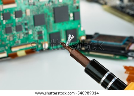 Screw and screwdriver closeup of electronic circuit board background #540989014