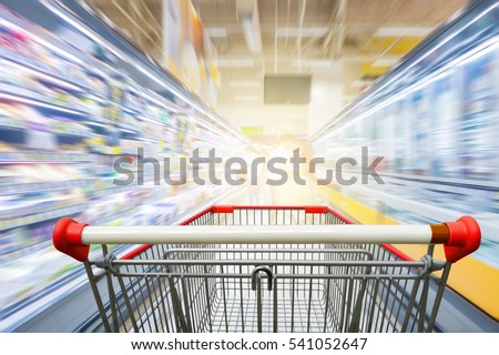 Supermarket aisle with empty red shopping cart Royalty-Free Stock Photo #541052647