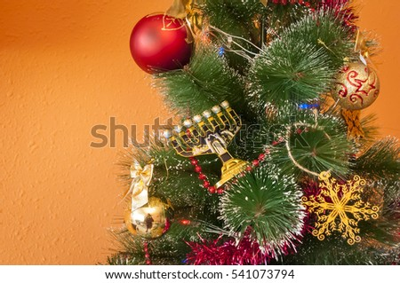 Jewish menorah on a decorated Christmas (New Year) tree. In December 2016 Jewish holiday Hanukkah coincides with Christmas and New Year.
