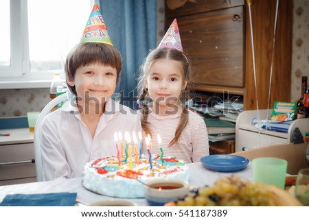 brother and sister sitting at home cake