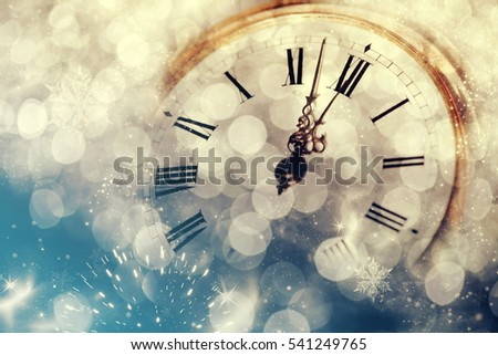 New Year's at midnight - Old clock with stars snowflakes and holiday lights #541249765