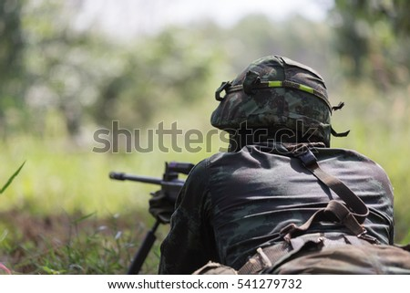 Unidentified Thai soldier laying down on ground to target with his gun , back side view #541279732
