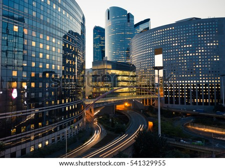 Night architecture - skyscrapers with glass facade. Modern buildings in Paris business district. Evening dynamic traffic on a street. Economy and finances concept. Copy space for text. Toned #541329955