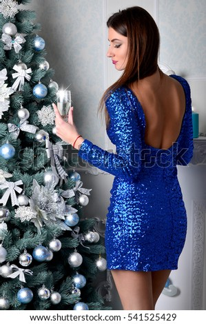Young beautiful girl in an elegant blue dress around a Christmas tree raises a glass of champagne during the New Year celebration. European Christmas traditions #541525429