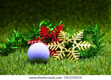 Golf ball with Christmas ornament on green grass.