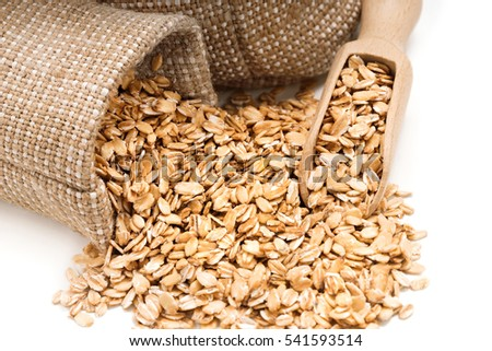 Close up oatmeal in burlap sack with wooden scoop on white background. Healthy food. Top view, high resolution product #541593514