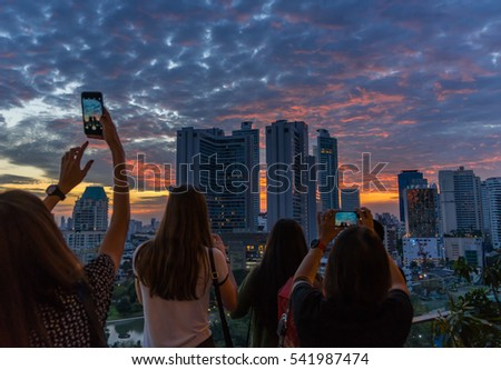 People taking photos of sunset and cityscape at dusk in Bangkok, Thailand.