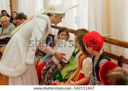 Odessa, Ukraine - December 22, 2016: Children's Christmas New Year's concert. Children play with Snow Maiden and Santa Claus. Emotional bright children's show in elementary school #542111647